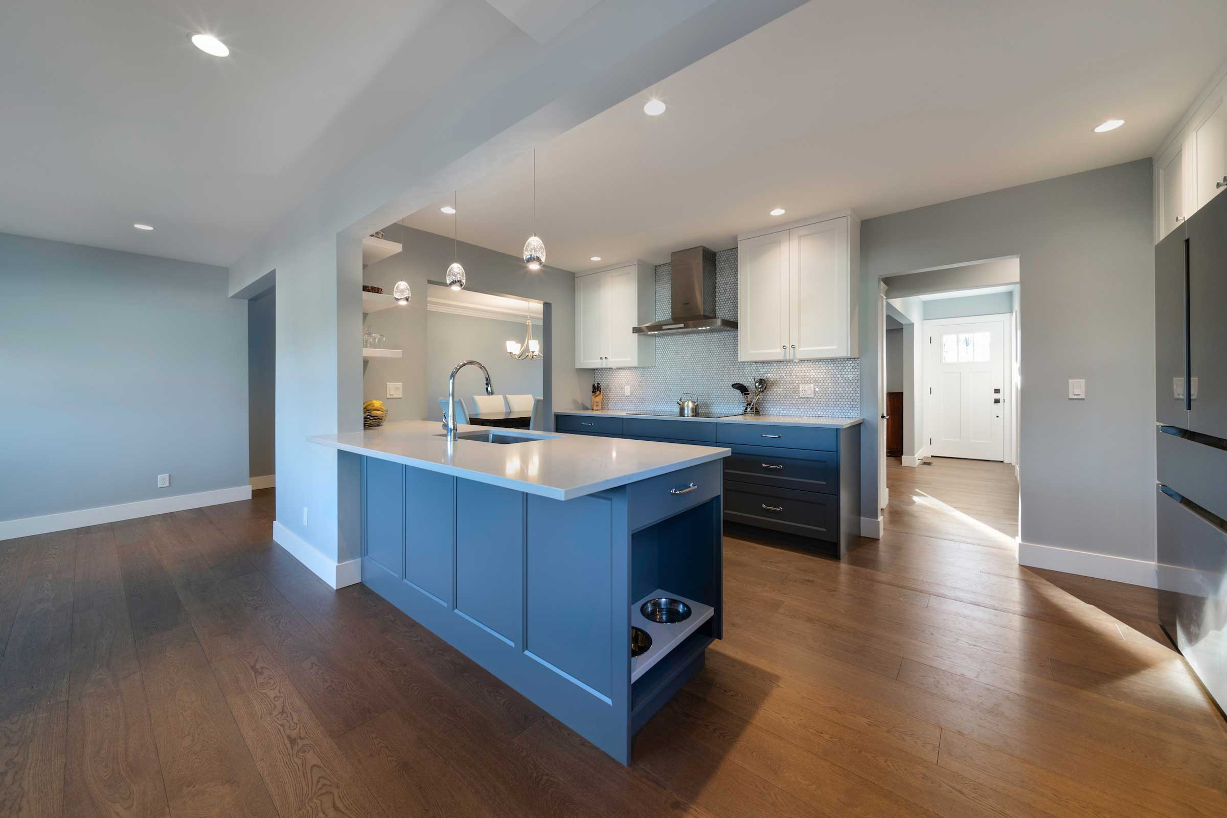 renovated kitchen with blue cupboards and hardwood floor