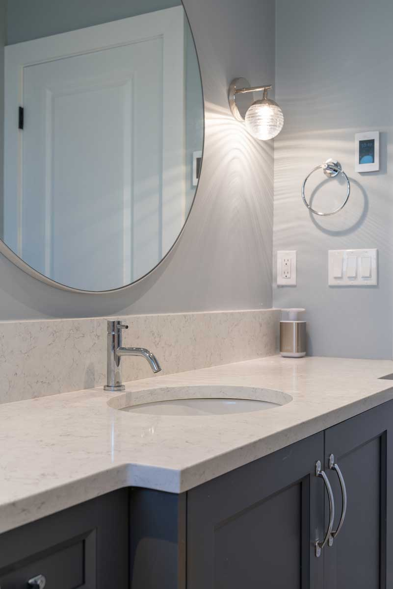 renovated bathroom sink and oval mirror