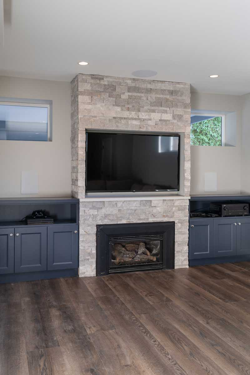 renovated basement fireplace and tv inset